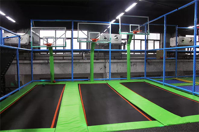Indoor trampoline park with basketball hoops